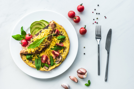 top view of homemade omelette with cherry tomatoes, avocado pieces and cutlery on white marble surface Imagens - 108856673