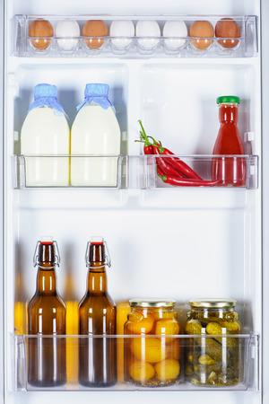 eggs, bottles of milk and preserved vegetables in fridge Banco de Imagens