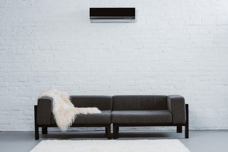 air conditioner hanging on white brick wall at living room Фото со стока