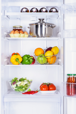 fruits, vegetables and pan with eggs in fridge