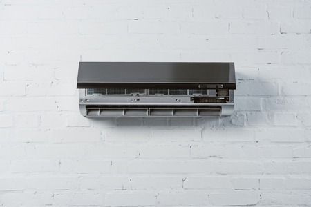 modern air conditioner with opened front plate hanging on white brick wall Banque d'images - 108856800