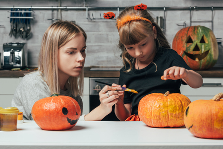 young woman and little sister painting pumpkins for halloween together in kitchen at home Stock Photo