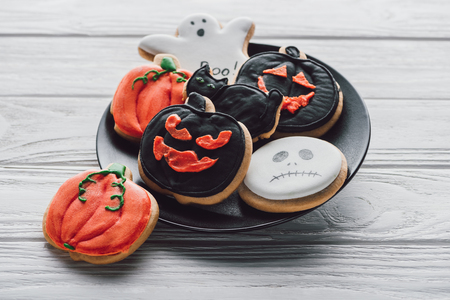 close up view of plate with spooky halloween cookies on wooden table Stock Photo