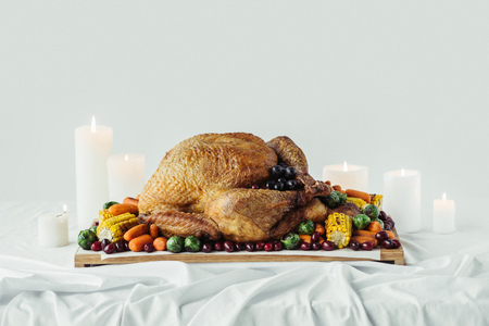 close up view of arranged candles, festive turkey with roasted vegetables for holiday dinner on tabletop, thanksgiving holiday concept Stock Photo