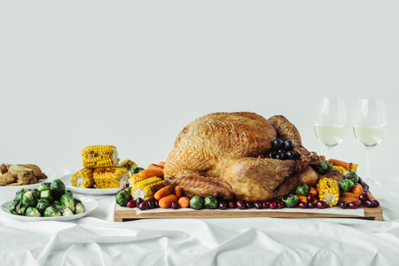 close up view of holiday dinner table set with roasted turkey, vegetables and glasses of wine on grey background, thanksgiving holiday concept 스톡 콘텐츠
