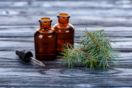 bottles of natural herbal essential oils, fir twigs and pipette on wooden table