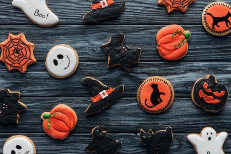 top view of arranged delicious halloween cookies on wooden table