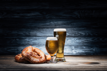 two glasses of tasty beer and yummy pretzels on wooden table, oktoberfest concept