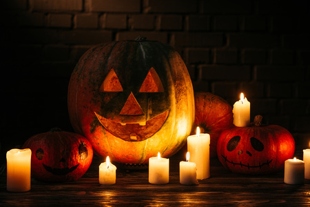 halloween carved pumpkins on wooden table in front of brick wall