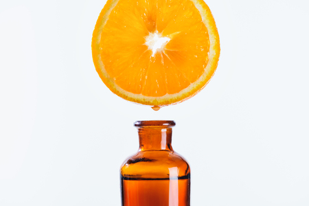 aromatic juice of orange piece dripping into bottle of natural herbal essential oil isolated on white