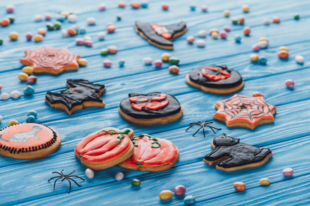 colorful candies and homemade halloween cookies on blue wooden table