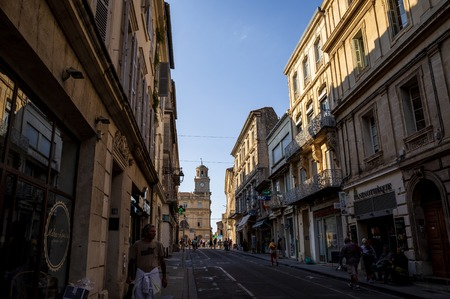 AVIGNON, FRANCE - JUNE 18, 2018: people walking on street with beautiful old architecture, Avignon, France