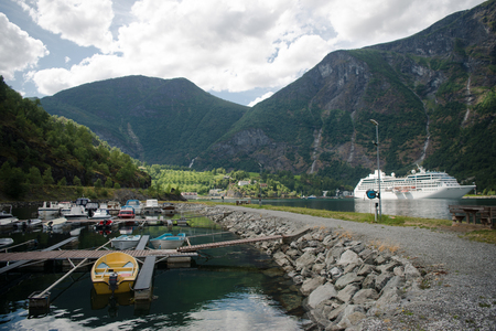 AURLANDSFJORD, FLAM, NORWAY - 27 JULY, 2018: cruise liner and boats moored near majestic mountains at Aurlandsfjord, Flam (Aurlandsfjorden), Norway