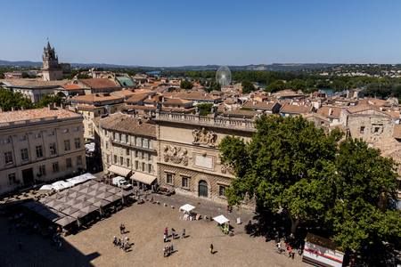 AVIGNON, FRANCE - JUNE 18, 2018: aerial view of pedestrians on streets and square, beautiful old architecture and scenic cityscape of historical european city Avignon
