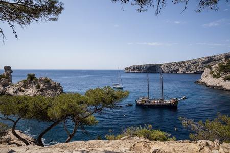 CALANQUES DE MARSEILLE, FRANCE - JUNE 18, 2018: boats in calm harbour and beautiful cliffs in Calanques de Marseille (Massif des Calanques), france Editorial