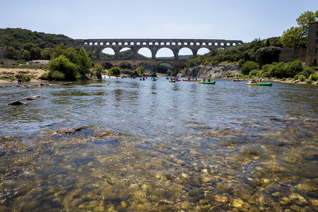 PROVENCE, FRANCE - JUNE 18, 2018: Pont du Gard (bridge across Gard) and people swimming on boats in Provence, France Archivio Fotografico - 111375568