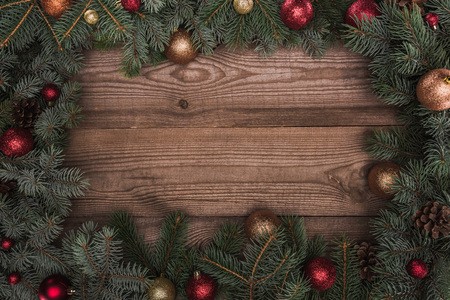 beautiful evergreen coniferous branches with shiny baubles and pine cones on wooden background