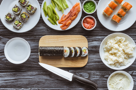 top view of delicious sliced sushi roll, knife and ingredients on wooden table