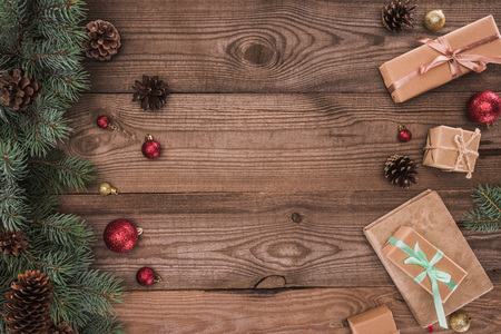 top view of coniferous branches with pine cones, baubles and christmas presents on wooden background