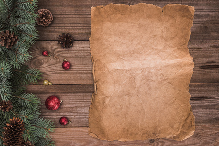 top view of blank parchment, coniferous branches with pine cones and baubles, christmas background