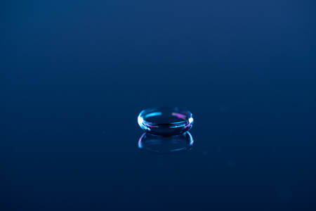 close up view of contact lense on blue backdrop Stock Photo