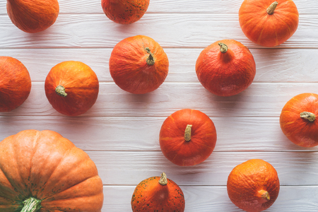 top view of scattered autumnal orange pumpkins on wooden tabletop