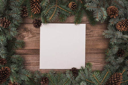 top view of blank card and coniferous branches with pine cones on wooden background