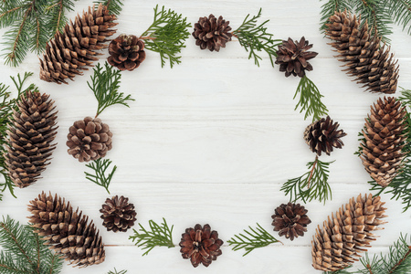 top view of evergreen coniferous twigs and pine cones on white wooden background Banco de Imagens