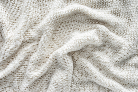 full frame of wavy white knitted cloth as background