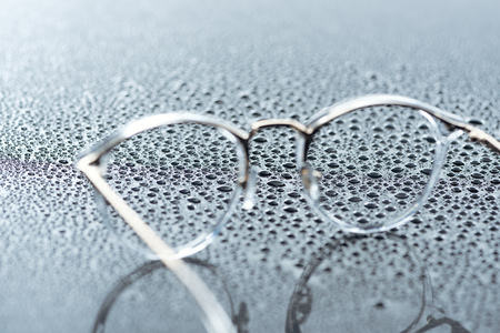 close up view of eyeglasses and water drops on grey backdrop
