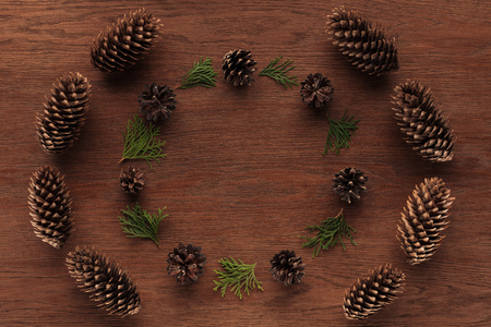 top view of beautiful evergreen coniferous twigs and pine cones on wooden background Banco de Imagens