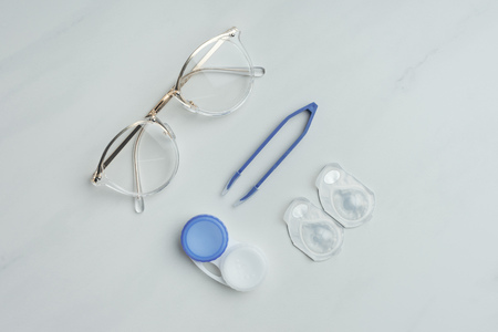 flat lay with eyeglasses, contact lenses containers and tweezers arranged on white surface