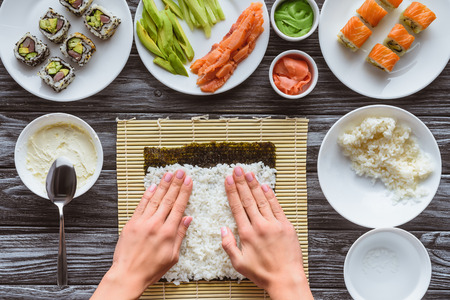 partial top view of person preparing sushi with rice and nori, gourmet ingredients on table Banco de Imagens