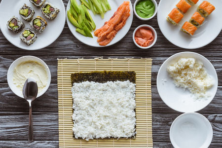 top view of rice, nori and ingredients for sushi on wooden table