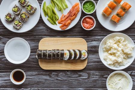 bovenaanzicht van heerlijke gesneden sushi roll en ingrediënten op houten tafel Stockfoto