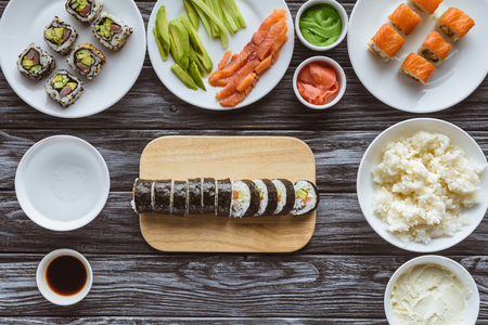 Draufsicht auf köstliche geschnittene Sushi-Rolle und Zutaten auf Holztisch Standard-Bild
