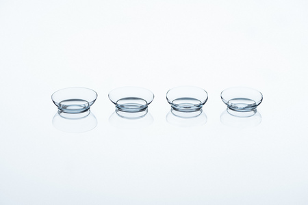 close up view of contact lenses arranged on white backdrop Foto de archivo