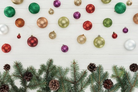 beautiful shiny colorful christmas balls and fir twigs with pine cones on white wooden background Banco de Imagens