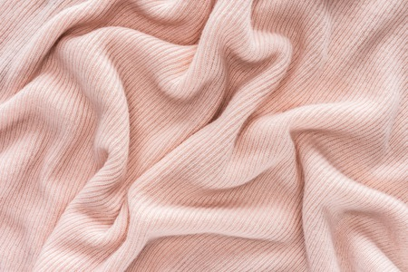 full frame of pink folded woolen fabric background