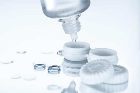 Nahaufnahme der Kontaktlinsen und ihrer Speicherausrüstung auf weißem Hintergrund