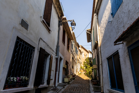 low angle view of cozy narrow street with traditional white houses in provence, france