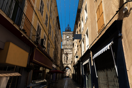 low angle view of cozy narrow street and old historic clock tower, provence, france