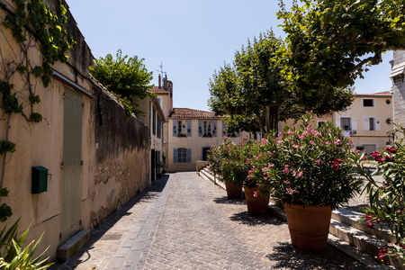 beautiful cozy narrow street with traditional houses, green trees and blooming flowers in pots, provence, france 版權商用圖片