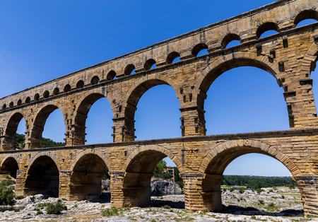 Pont du Gard (bridge across Gard) ancient Roman aqueduct across Gardon River at sunny day in  Provence, France Standard-Bild - 108918204