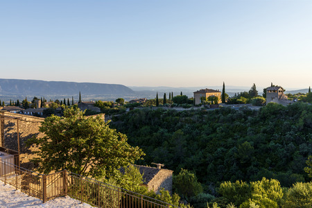 scenic view of traditional houses, green vegetation and distant mountains in provence, france