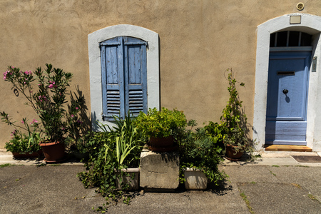 traditional old house with blue wooden doors and shutters and green plants in pots outdoor in provence, france