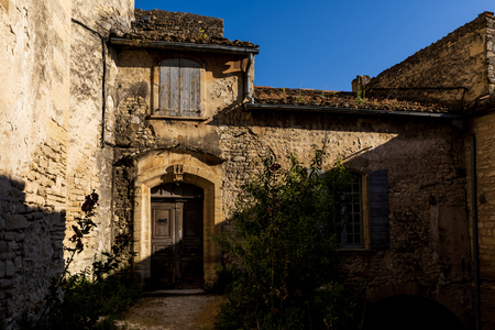 beautiful old stone building with wooden doors and shutters at sunny day, provence, france Stock Photo