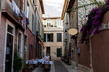 cozy narrow street with traditional houses and outdoor cafe in provence, france