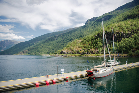 yachts moored in calm harbour and beautiful mountains, Aurlandsfjord, Flam (Aurlandsfjorden), Norway Stock Photo