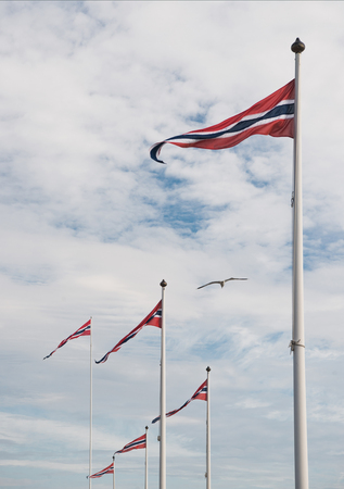 low angle view of norwegian flags against cloudy sky, Hamar, Hedmark, Norway Stock Photo